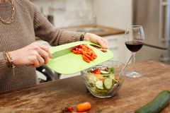 Accurate lady in beige sweater adding chopped tomatoes into glass bowl. Green plastic board. Accurate lady in beige sweater adding chopped tomatoes into glass stock image