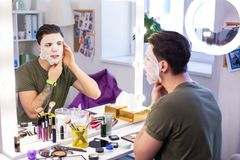 Accurate man correcting his smoothing face mask while getting ready. Spacious mirror. Accurate man correcting his smoothing face mask while getting ready in stock photography