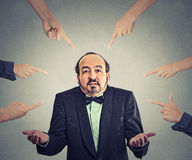 Accusation of guilty arrogant businessman who shrugs shoulders. Concept of accusation of guilty arrogant businessman. Middle aged man judged by different people Royalty Free Stock Photos