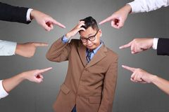 Accusation of a Guilty Businessman. Accusation guilty business person. Asian businessman get upset with many fingers pointing at him over grey background royalty free illustration