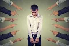 Accusation of guilty guy. Sad upset man looking down many fingers pointing at him Stock Photography