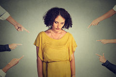 Accusation guilty person girl. Sad embarrassed woman looking down many fingers pointing at her Royalty Free Stock Images