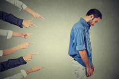 Accusation of guilty person guy, young man. Concept of accusation guilty person guy. Side profile sad upset man looking down many fingers pointing at his back Royalty Free Stock Photos