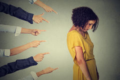 Accusation guilty person. Sad upset woman looking down many fingers pointing at her back. Concept accusation guilty person girl. Side profile sad upset woman Royalty Free Stock Photography