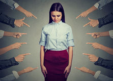 Accusation of guilty person. Sad woman looking down fingers pointing at her stock photography