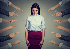 Accusation of guilty person. Upset woman, many fingers pointing at her. Concept of accusation of guilty person. Upset woman looking at camera many fingers Royalty Free Stock Images