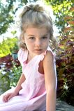 Accusing Garden Nympth. Young girl with blonde curls solemnly stares at camera.  She has on pink sleeveless shift Stock Photography
