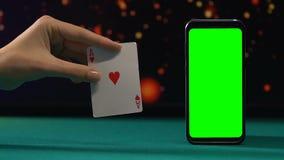 Ace av hjärtor nära den gröna skärmsmartphonen som segrar kombination, online-kasino stock video