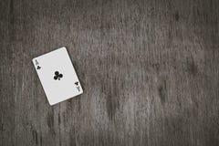 Ace av klubbacloseupen som spelar kort på en träbakgrund Risk- och dobbleribakgrund, abstrakt begrepp och lekbegrepp Arkivfoto