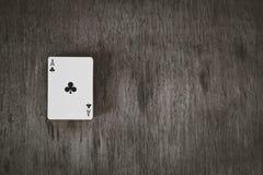 Ace av klubbor Spela kort på en träbakgrund Risk- och dobbleribakgrund, abstrakt begrepp och lekbegrepp Royaltyfri Fotografi