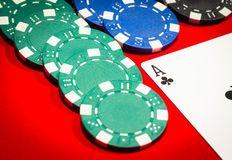 Ace of clubs and chips on a red table Stock Photos
