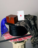 Ace of Hearts Playing Card on top hat. Ace of hearts playing card resting on a top hat with scarf and cane, magic box, playing cards face down and wand Royalty Free Stock Images