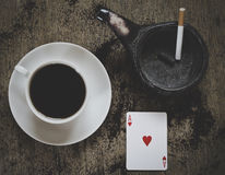 Ace of hearts playing cards with coffee cup and ashtray Royalty Free Stock Photo