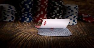 Ace-Karte und Pokerchips, auf einem hölzernen Hintergrund Stockbilder