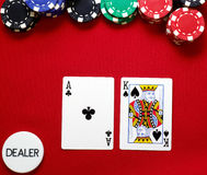Ace King offsuited on the button. Poker hand, ace king off suited on the button on red felt with red black blue and green chips Royalty Free Stock Photos