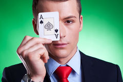 Ace over eye. Business man holding the ace of spades over his eye on green background Stock Image