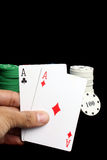 Ace Pair. A great poker hand of two aces with casino chips in the backdrop, isolated on black studio background Royalty Free Stock Photo