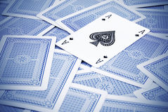 Ace of spade. On top of blue playing cards stock image