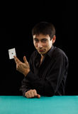 Ace of spades. Beautiful young gambler man in black shirt sitting at the playing table with ace of spades in his hand isolated on black background Royalty Free Stock Photo