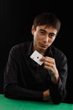 Ace of spades. Beautiful young gambler man in black shirt sitting at the playing table with ace of spades in his hand isolated on black background Stock Photography