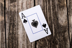 Ace of Spades Card on Wood. Ace of Spades from a deck of cards laying on vintage wood table background - old west salon style Royalty Free Stock Images