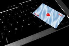 Ace van hartenkaart ligt bovenop een laptop toetsenbord stock foto's