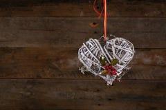 Acebo blanco adornado de la cinta de las ramitas de la guirnalda de la Navidad de la forma del corazón Fotografía de archivo libre de regalías