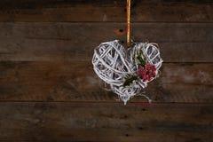 Acebo blanco adornado de la cinta de las ramitas de la guirnalda de la Navidad de la forma del corazón Imagen de archivo