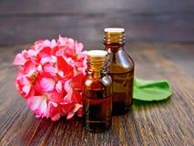 Aceite con los geranios rosados a bordo Fotos de archivo libres de regalías