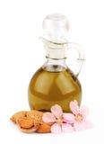 Aceite de almendra y tuercas de la almendra con las flores Imagen de archivo libre de regalías