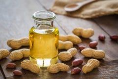 Aceite de cacahuete en la botella de cristal y cacahuetes en la tabla de madera Foto de archivo libre de regalías