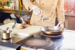 Aceite de cocina de colada del cocinero en el sartén Fotos de archivo