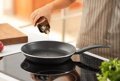 Aceite de cocina de colada de la mujer de la botella en el sartén imagen de archivo libre de regalías