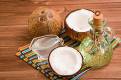 Aceite de coco, leche y cocos en una tabla de madera Imagenes de archivo