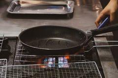Aceite de colada del cocinero en el sartén, cocinero que cocina la comida en la cocina imagen de archivo libre de regalías