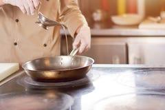 Aceite de colada del cocinero en sartén Imagen de archivo libre de regalías