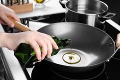 Aceite de colada de la mujer de la botella sobre el wok imagenes de archivo