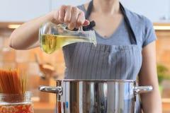 Aceite de colada de la mujer del tarro en el sartén en cocina imágenes de archivo libres de regalías