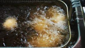 Aceite de ebullición en la fritura El cocinero lanza los anillos de espuma en la sartén profunda cooking Anillos de espuma de la  metrajes