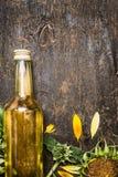 Aceite de girasol en la botella de cristal y girasoles en fondo de madera rústico Fotografía de archivo