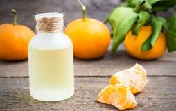Aceite de la mandarina en una botella de cristal con las mandarinas frescas imagen de archivo libre de regalías