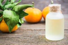Aceite de la mandarina en una botella de cristal con las mandarinas frescas imagenes de archivo