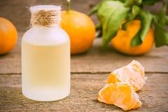 Aceite de la mandarina en una botella de cristal con las mandarinas frescas foto de archivo libre de regalías