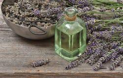 Aceite de lavanda con las flores frescas en fondo de madera St del vintage Fotos de archivo