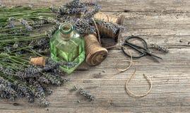 Aceite de lavanda con las flores frescas, las tijeras y la decoración del vintage Fotografía de archivo libre de regalías