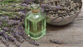 Aceite de lavanda con las flores frescas y las tijeras en backgroun de madera Imagenes de archivo