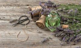 Aceite de lavanda con las flores frescas y las tijeras en backgroun de madera Foto de archivo libre de regalías