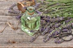 Aceite de lavanda herbario con el ramo de las flores frescas en backgro de madera Imagenes de archivo
