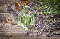 Aceite de lavanda herbario con el ramo de las flores frescas en backgro de madera Imagen de archivo