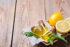 Aceite de limón esencial orgánico con las hojas y la fruta del verde Foto de archivo